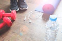Concept de forme physique avec la bouteille de l'eau, espadrilles, haltères rouges sur le plancher en bois, l'espace de copie Photographie stock libre de droits
