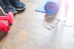Concept de forme physique avec la bouteille de l'eau, espadrilles, haltères rouges sur le plancher en bois, l'espace de copie Photo libre de droits