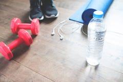 Concept de forme physique avec la bouteille de l'eau, espadrilles, haltères rouges sur le plancher en bois, l'espace de copie Image libre de droits