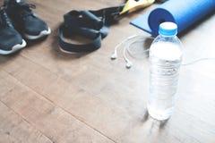 Concept de forme physique avec la bouteille de l'eau, espadrilles sur le plancher en bois, l'espace de copie Images stock