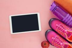 concept de forme physique avec la bouteille de l'eau, de serviette, de legs de comprimé et de chaussures roses de sport de femme  Photographie stock