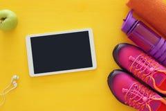 concept de forme physique avec la bouteille de l'eau, de serviette, de legs de comprimé et de chaussures roses de sport de femme  Images stock