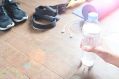 Concept de forme physique avec la main de femme tenant la bouteille de l'eau, espadrilles, TRX sur le plancher en bois, l'espace  Image stock