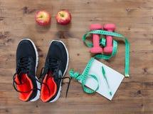 Concept de forme physique avec la pomme de carnet d'espadrilles et la bande de mesure Image libre de droits
