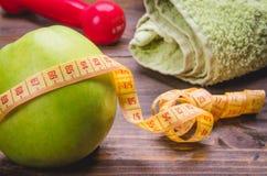Concept de forme physique avec la pomme, le centimètre, la serviette et les haltères Photographie stock libre de droits
