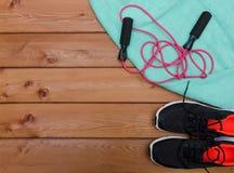 Concept de forme physique avec la serviette d'espadrilles et corde à sauter sur en bois Photos stock