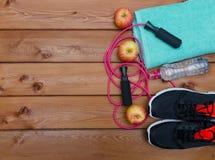 Concept de forme physique avec la serviette d'espadrilles, la pomme et la corde à sauter Photographie stock