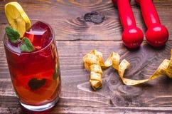 Concept de forme physique avec le cocktail avec un citron, des haltères et le centimètre Image stock