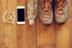 Concept de forme physique avec le téléphone portable avec les écouteurs, la serviette et les chaussures de sport au-dessus du fon Photos libres de droits