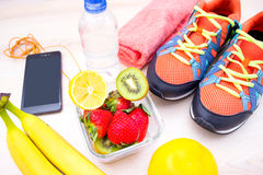 Concept de forme physique avec le téléphone portable avec les écouteurs, la serviette et les chaussures de sport au-dessus du fon Photographie stock