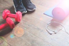 Concept de forme physique avec les espadrilles, haltères rouges sur le plancher en bois, l'espace de copie Image libre de droits
