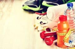 Concept de forme physique avec les haltères, le jus de fruit et les vêtements de sport Photos stock