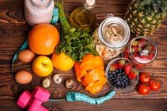 Concept de forme physique avec les haltères roses, les baies fraîches, les fruits, les légumes et les oeufs photo libre de droits