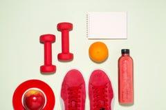 Concept de forme physique Bottl de jus d'espadrilles, de pomme, d'haltère et de fruit Image libre de droits