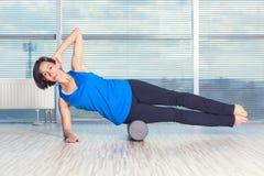Concept de forme physique, de sport, de formation et de mode de vie - femme faisant des pilates sur le plancher avec le rouleau d photos stock
