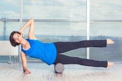 Concept de forme physique, de sport, de formation et de mode de vie - femme faisant des pilates sur le plancher avec le rouleau d photographie stock