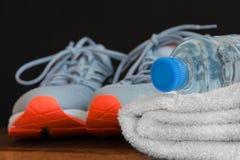 Concept de forme physique Les espadrilles folâtrent des chaussures, la serviette, bouteille de l'eau sur le fond en bois Image libre de droits
