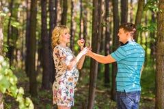 Concept de grossesse, de famille, de bonheur et d'amusement - l'homme et la femme enceinte ont l'amusement avec la sucrerie dans  Images stock