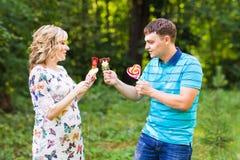 Concept de grossesse, de famille, de bonheur et d'amusement - l'homme et la femme enceinte ont l'amusement avec la sucrerie dans  Photographie stock libre de droits