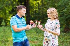 Concept de grossesse, de famille, de bonheur et d'amusement - l'homme et la femme enceinte ont l'amusement avec la sucrerie dans  Photographie stock