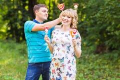 Concept de grossesse, de famille, de bonheur et d'amusement - l'homme et la femme enceinte ont l'amusement avec la sucrerie dans  Photo stock