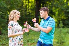 Concept de grossesse, de famille, de bonheur et d'amusement - l'homme et la femme enceinte ont l'amusement avec la sucrerie dans  Photos libres de droits