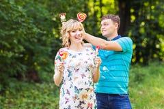 Concept de grossesse, de famille, de bonheur et d'amusement - l'homme et la femme enceinte ont l'amusement avec la sucrerie dans  Images libres de droits