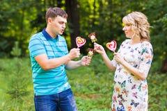 Concept de grossesse, de famille, de bonheur et d'amusement - l'homme et la femme enceinte ont l'amusement avec la sucrerie dans  Image stock