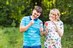 Concept de grossesse, de famille, de bonheur et d'amusement - l'homme et la femme enceinte ont l'amusement avec la sucrerie dans  Photo libre de droits