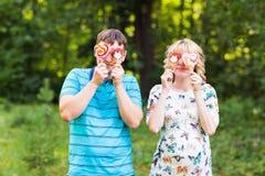 Concept de grossesse, de famille, de bonheur et d'amusement - l'homme et la femme enceinte ont l'amusement avec la sucrerie dans  Photos stock