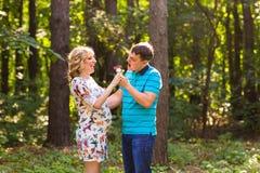 Concept de grossesse, de famille, de bonheur et d'amusement - l'homme et la femme enceinte ont l'amusement dans le parc Photographie stock libre de droits