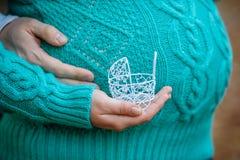 Concept de grossesse : gonflez-vous avec la main tenant la petite poussette de jouet dans l'avant Photos libres de droits