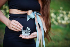 Concept de grossesse : gonflez-vous avec la main tenant la petite poussette de jouet dans l'avant sur le fond rose Photo stock