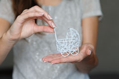 Concept de grossesse : main de femme tenant la petite poussette de jouet dans l'avant Photo libre de droits