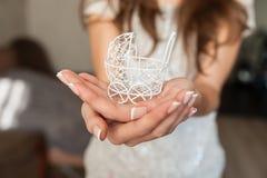 Concept de grossesse : main de femme tenant la petite poussette de jouet dans l'avant Image libre de droits