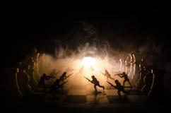 Concept de guerre Silhouettes des soldats sur l'échiquier Concept de guerre Silhouettes militaires combattant la scène sur le fon Photographie stock libre de droits