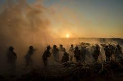 Concept de guerre Silhouettes militaires et réservoirs combattant la scène sur le fond de ciel de brouillard de guerre, silhouett Photographie stock libre de droits