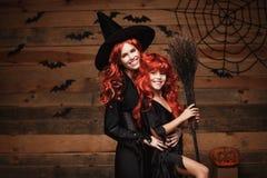 Concept de Halloween - belle mère caucasienne et sa fille avec de longs cheveux rouges dans des costumes de sorcière célébrant la Photos stock