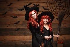 Concept de Halloween - belle mère caucasienne et sa fille avec de longs cheveux rouges dans des costumes de sorcière célébrant la Image stock
