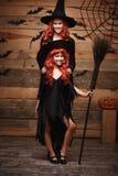 Concept de Halloween - belle mère caucasienne et sa fille avec de longs cheveux rouges dans des costumes de sorcière célébrant la Images stock