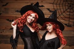 Concept de Halloween - belle mère caucasienne et sa fille avec de longs cheveux rouges dans des costumes de sorcière célébrant la image libre de droits