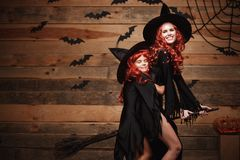 Concept de Halloween - belle mère caucasienne et sa fille avec de longs cheveux rouges dans des costumes de sorcière volant avec  Photo stock