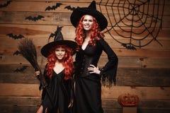 Concept de Halloween - belle mère caucasienne et sa fille avec de longs cheveux rouges dans la célébration de costumes de sorcièr Images libres de droits
