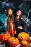 Concept de Halloween - belle mère caucasienne de plan rapproché et sa fille dans des costumes de sorcière célébrant la pose de Ha images libres de droits