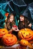 Concept de Halloween - belle mère caucasienne de plan rapproché et sa fille dans des costumes de sorcière célébrant la pose de Ha photos libres de droits