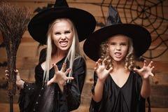 Concept de Halloween - belle mère caucasienne de plan rapproché et sa fille dans des costumes de sorcière célébrant Halloween pos photos stock