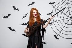 Concept de Halloween - la sorcière élégante heureuse ont plaisir à jouer avec la partie de Halloween de manche à balai photo libre de droits