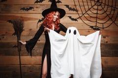 Concept de Halloween - mère de sorcière et peu de fantôme blanc faisant le des bonbons ou un sort célébrant Halloween posant avec photo stock