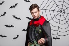 Concept de Halloween de vampire - le portrait du vampire caucasien beau tenant beau rouge s'est levé Image libre de droits