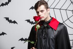 Concept de Halloween de vampire - le portrait du vampire caucasien beau tenant beau rouge s'est levé Photos libres de droits